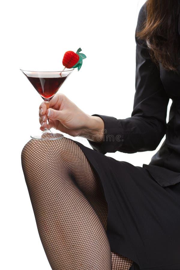 Γυναίκα στις μαύρες γυναικείες κάλτσες διχτυών ψαρέματος που κρατά το κοκτέιλ στοκ φωτογραφίες με δικαίωμα ελεύθερης χρήσης