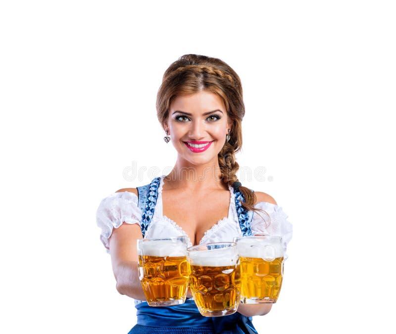 Γυναίκα στις παραδοσιακές βαυαρικές κούπες εκμετάλλευσης φορεμάτων της μπύρας στοκ φωτογραφίες