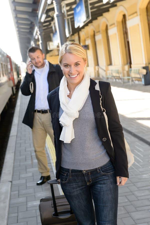 Γυναίκα στον άνδρα σταθμών τρένου στο κινητό τηλέφωνο στοκ φωτογραφία με δικαίωμα ελεύθερης χρήσης