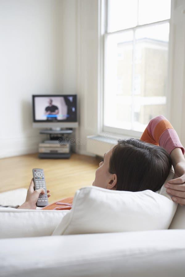 Γυναίκα στον καναπέ που προσέχει τη TV Στοκ Εικόνα