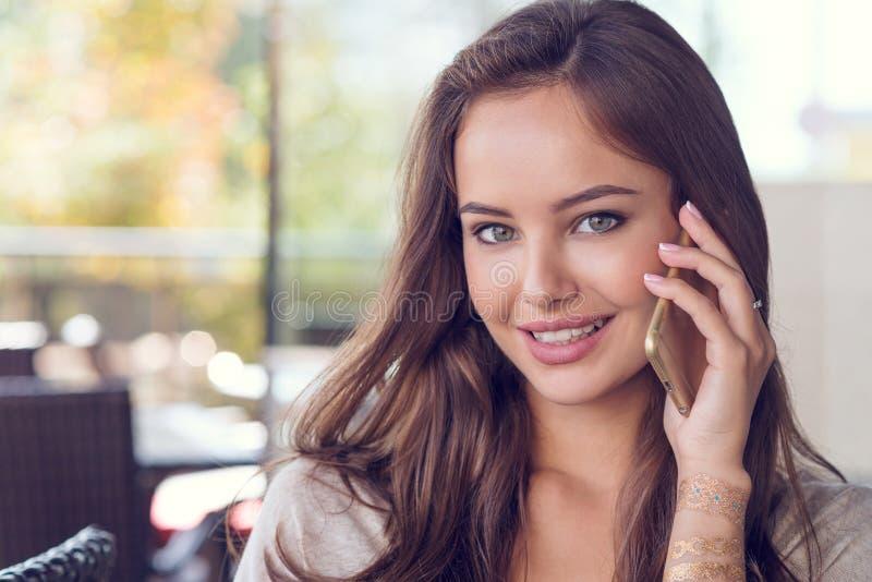 Γυναίκα στον καφέ κατανάλωσης καφέδων και χρησιμοποίηση του κινητού τηλεφώνου της στοκ εικόνες με δικαίωμα ελεύθερης χρήσης