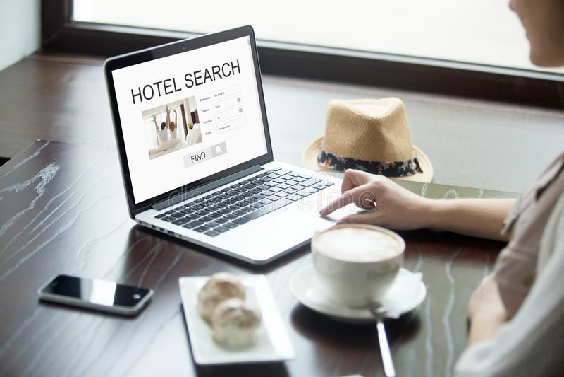 Γυναίκα στον καφέ που ψάχνει για το ξενοδοχείο στο lap-top, διακοπές προγραμματισμού στοκ εικόνα