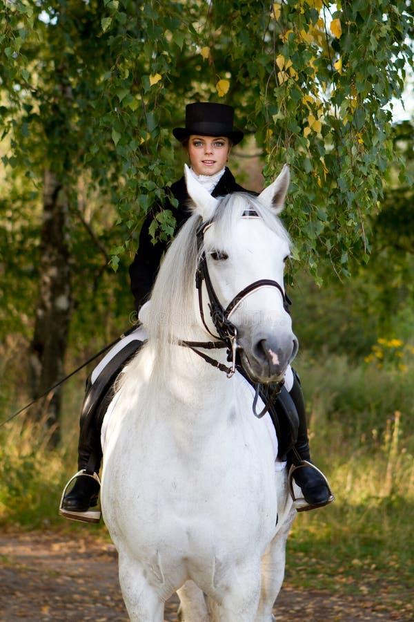 Γυναίκα στον ομοιόμορφο γύρο στο άσπρο άλογο στο πάρκο στοκ φωτογραφία με δικαίωμα ελεύθερης χρήσης