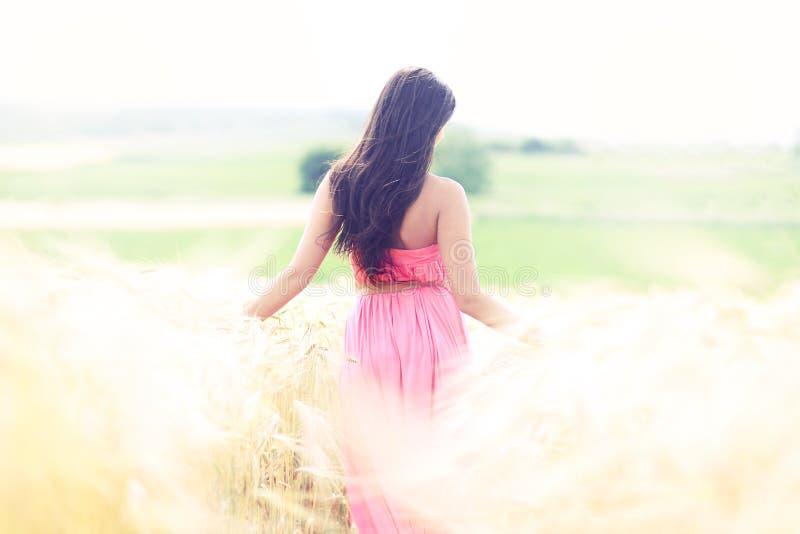 Γυναίκα στους τομείς ουρανού του χρυσού στοκ φωτογραφίες