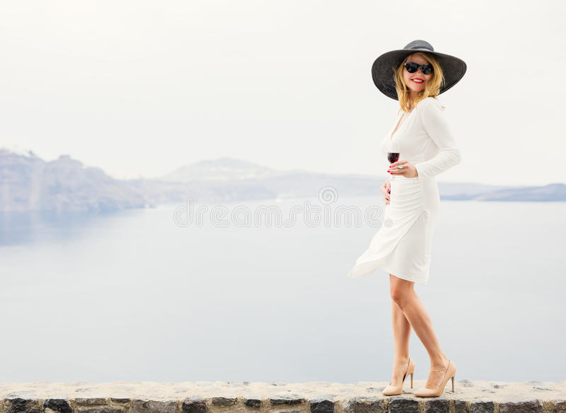 Γυναίκα στο άσπρο κρασί κατανάλωσης φορεμάτων και μαύρων καπέλων υπαίθρια στοκ εικόνα