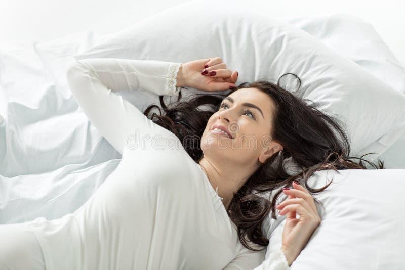 Γυναίκα στο άσπρο ξύπνημα πιτζαμάτων στο κρεβάτι στο σπίτι στοκ φωτογραφία με δικαίωμα ελεύθερης χρήσης