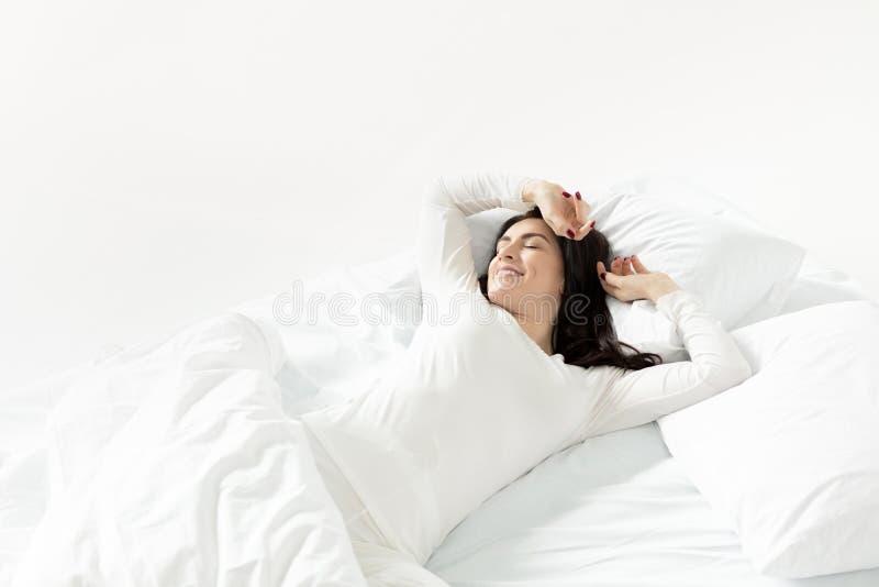 Γυναίκα στο άσπρο ξύπνημα πιτζαμάτων στο κρεβάτι στο σπίτι στοκ φωτογραφίες