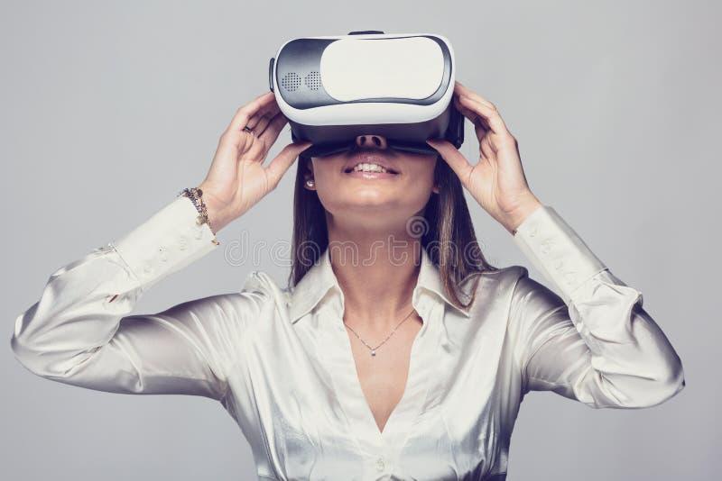 Γυναίκα στο άσπρο πουκάμισο που χρησιμοποιεί vr τα γυαλιά στοκ εικόνα