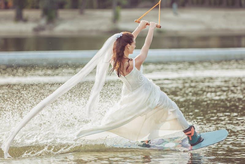 Γυναίκα στο άσπρο φόρεμα σε ένα σκι νερού στοκ εικόνες