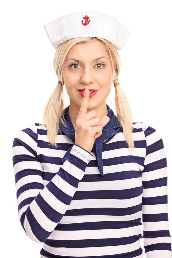 Γυναίκα στο δάχτυλο εκμετάλλευσης εξαρτήσεων ναυτικών στα χείλια της στοκ εικόνες