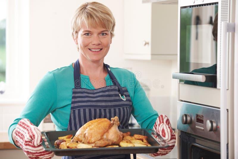 Γυναίκα στο δίσκο εκμετάλλευσης κουζινών με το κοτόπουλο ψητού στοκ εικόνα