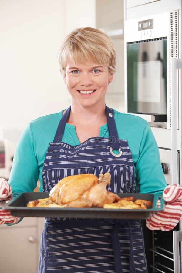 Γυναίκα στο δίσκο εκμετάλλευσης κουζινών με το κοτόπουλο ψητού στοκ φωτογραφία
