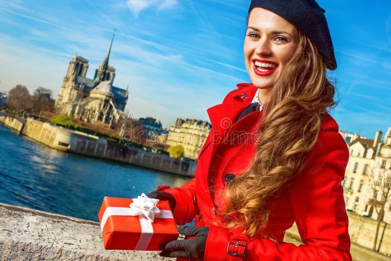 Γυναίκα στο ανάχωμα στο Παρίσι που παρουσιάζει κιβώτιο χριστουγεννιάτικου δώρου στοκ φωτογραφίες με δικαίωμα ελεύθερης χρήσης