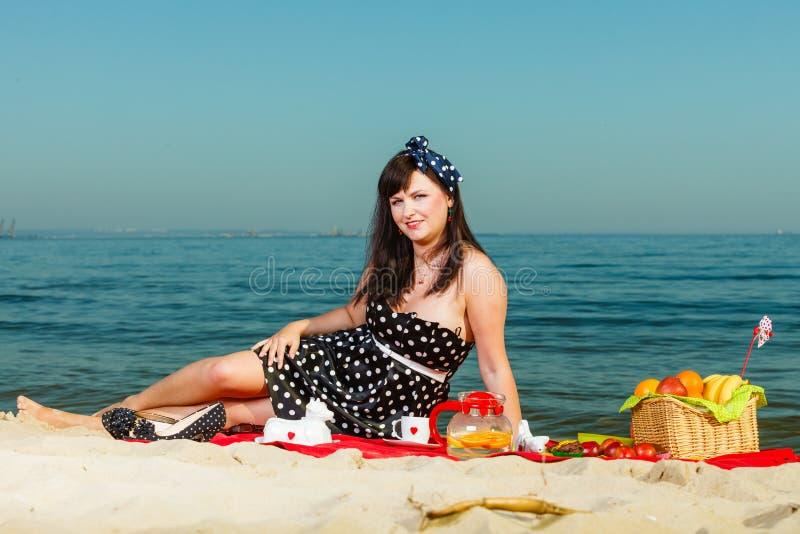 Γυναίκα στο αναδρομικό φόρεμα που έχει το πικ-νίκ κοντά στη θάλασσα στοκ εικόνες με δικαίωμα ελεύθερης χρήσης