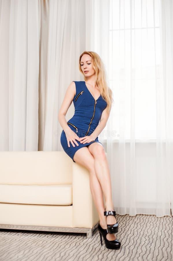 Γυναίκα στο απότομα μπλε φόρεμα στον καναπέ στο άσπρο δωμάτιο στοκ εικόνες