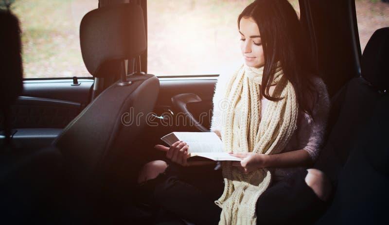 Γυναίκα στο αυτοκίνητο, έννοια πτώσης φθινοπώρου Χαμογελώντας όμορφο κορίτσι που διαβάζει ένα βιβλίο που κινείται στο αυτοκίνητο στοκ φωτογραφία με δικαίωμα ελεύθερης χρήσης