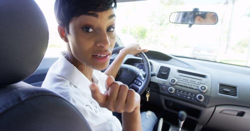 Γυναίκα στο αυτοκίνητο που κοιτάζει πέρα από τον ώμο και που φωνάζει στον επιβάτη στοκ φωτογραφία με δικαίωμα ελεύθερης χρήσης