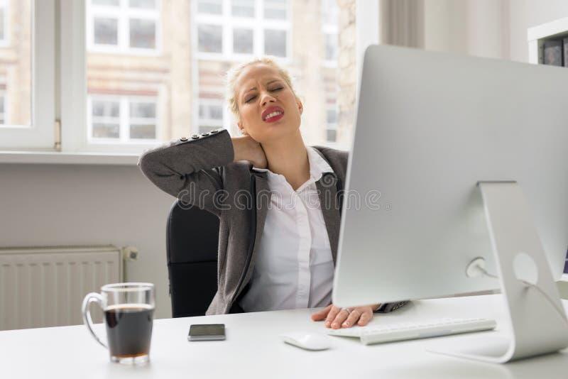 Γυναίκα στο γραφείο που κρατά το λαιμό της στον πόνο στοκ εικόνες