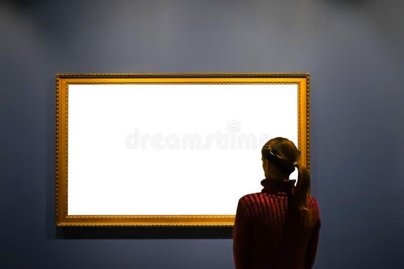 Γυναίκα στο δωμάτιο στοών που εξετάζει το κενό πλαίσιο εικόνων - χλευάστε επάνω την έννοια τέχνης στοκ εικόνες