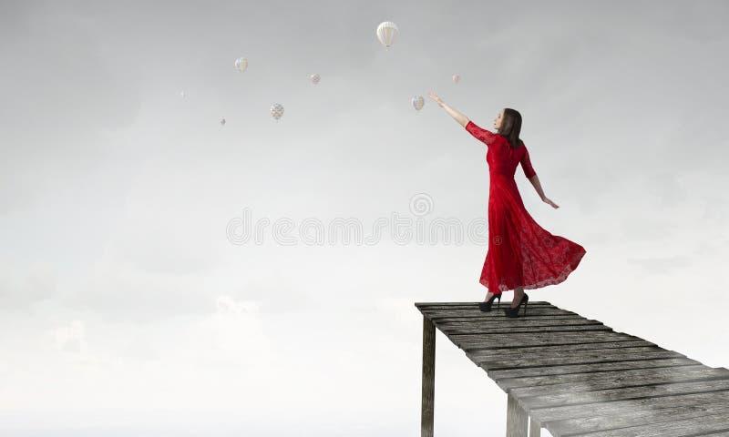 Γυναίκα στο εμπαθές κόκκινο φόρεμα Μικτά μέσα στοκ φωτογραφία