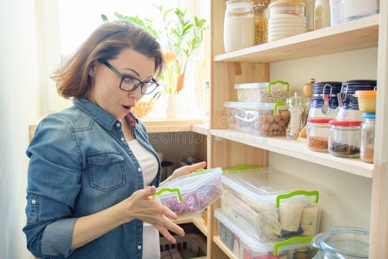 Γυναίκα στο εμπορευματοκιβώτιο εκμετάλλευσης οψοφυλακίων με το κόκκινο πικρό πιπέρι τσίλι Γραφείο αποθήκευσης στην κουζίνα στοκ φωτογραφίες με δικαίωμα ελεύθερης χρήσης