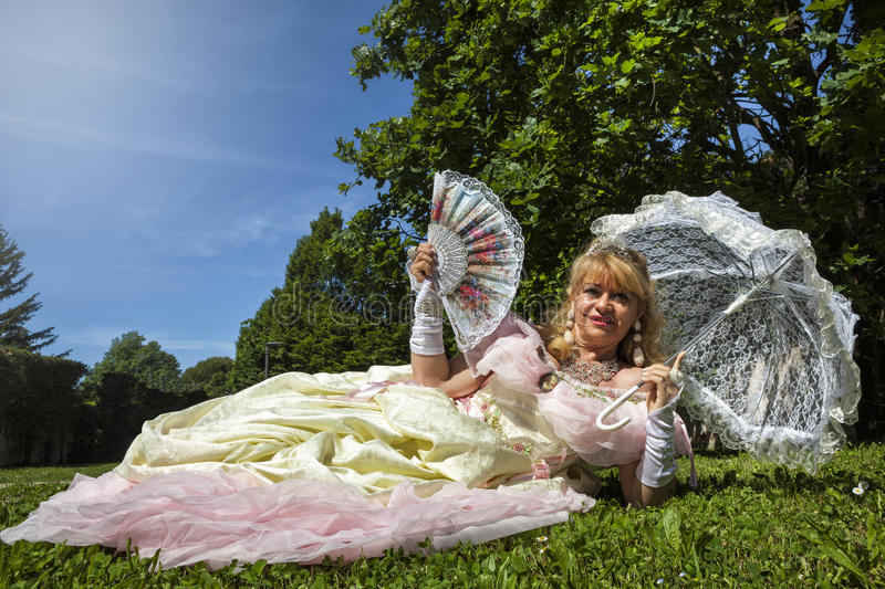 Γυναίκα στο ενετικό κοστούμι που βρίσκεται στο πράσινο πάρκο με την άσπρη ομπρέλα στοκ φωτογραφία