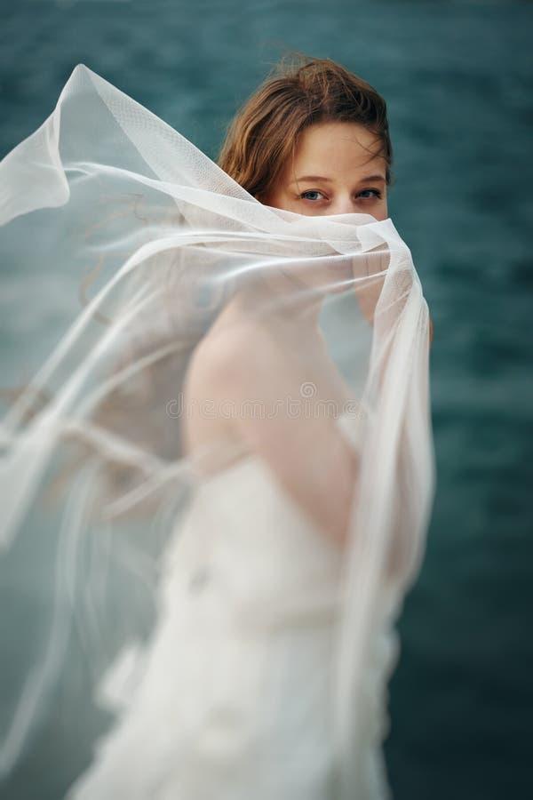 Γυναίκα στο λευκό κοντά στη θυελλώδη θάλασσα στοκ εικόνα