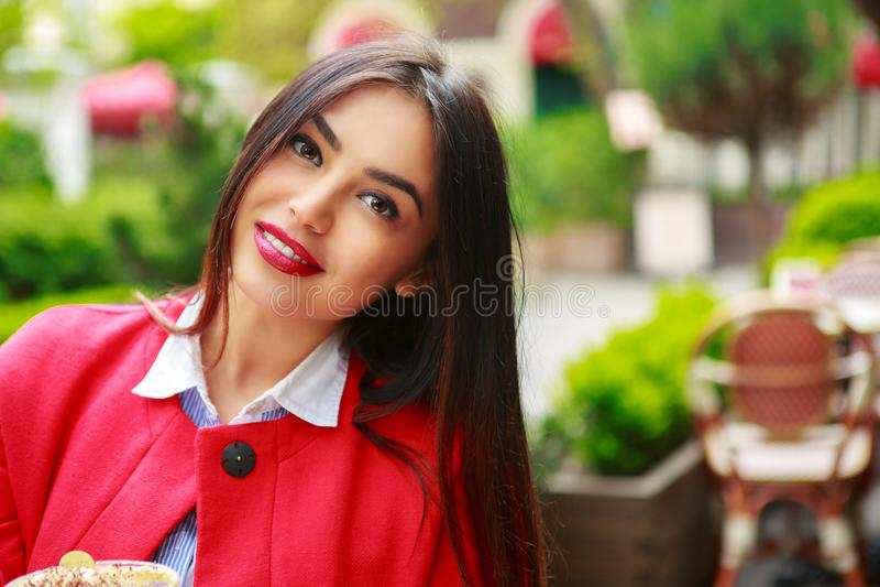 Γυναίκα στο ευτυχές χαμόγελο καφετεριών καφέδων που εξετάζει τη κάμερα στοκ φωτογραφία με δικαίωμα ελεύθερης χρήσης