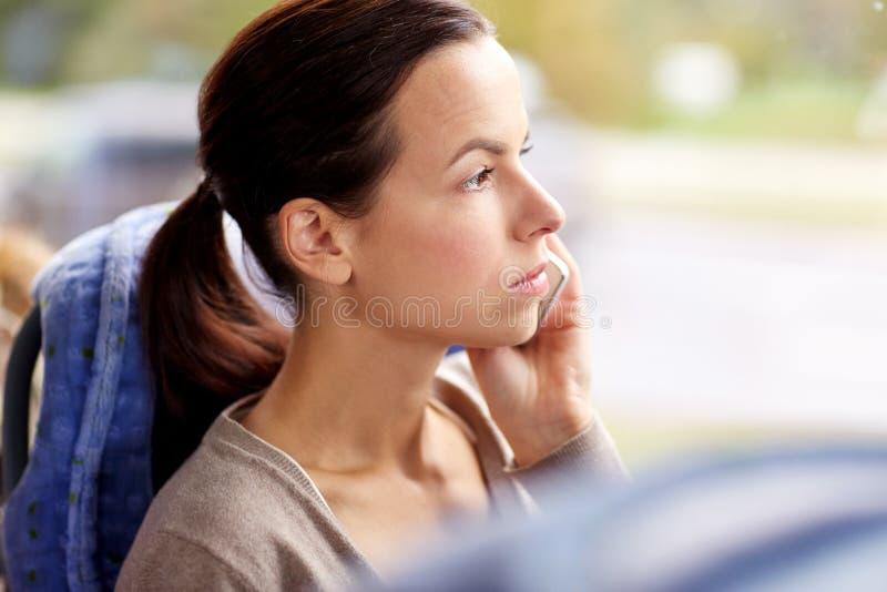 Γυναίκα στο λεωφορείο ταξιδιού που καλεί το smartphone στοκ εικόνες
