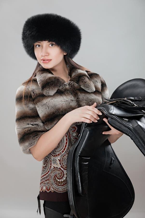 Γυναίκα στο θερμό ιματισμό με το κάθισμα για ένα άλογο στοκ φωτογραφία με δικαίωμα ελεύθερης χρήσης