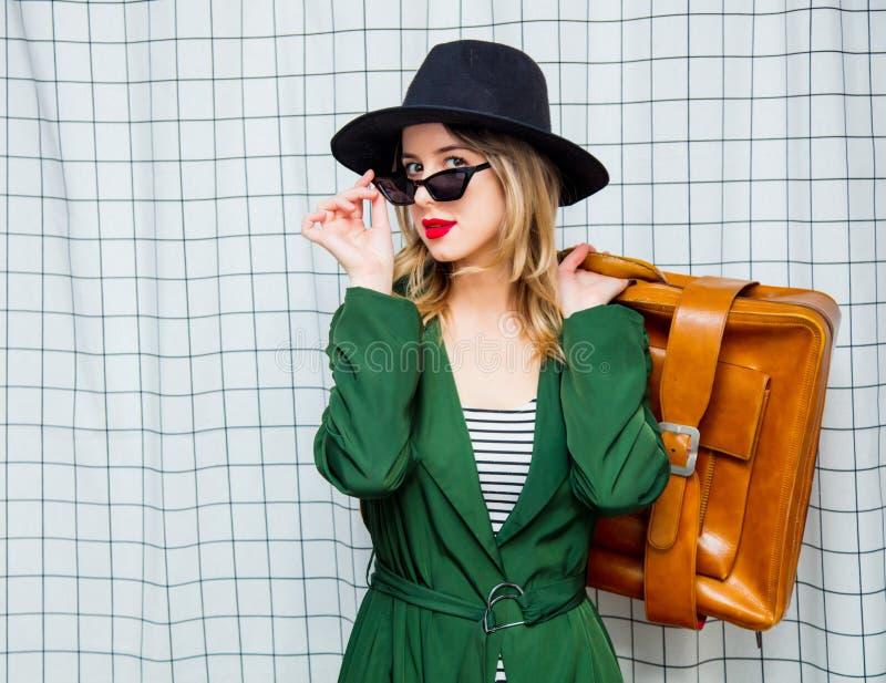 Γυναίκα στο καπέλο και πράσινος επενδύτης στο ύφος της δεκαετίας του '90 με τη βαλίτσα ταξιδιού στοκ φωτογραφία