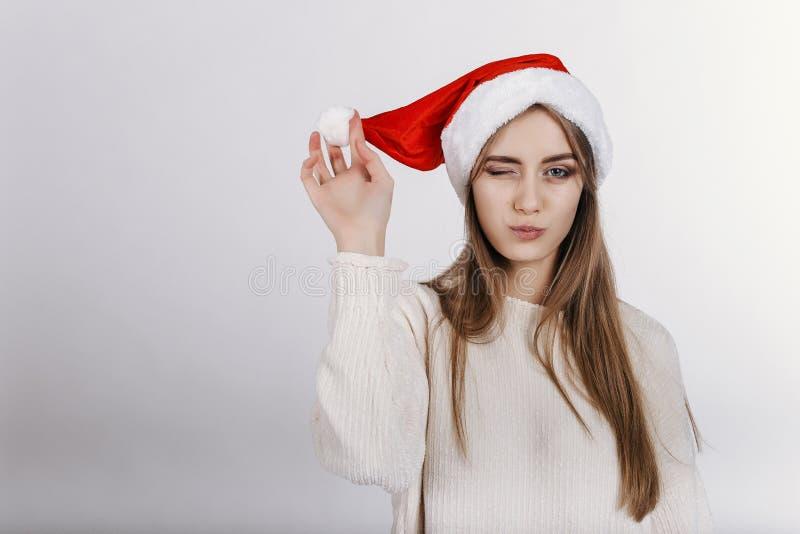 Γυναίκα στο καπέλο Santa που κλείνει το μάτι στη κάμερα στοκ φωτογραφία