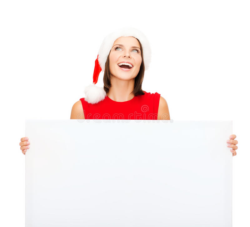 Γυναίκα στο καπέλο αρωγών santa με τον κενό λευκό πίνακα στοκ φωτογραφίες με δικαίωμα ελεύθερης χρήσης