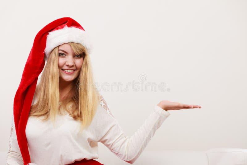 Γυναίκα στο καπέλο santa με το κενό χέρι για το διάστημα αντιγράφων στοκ εικόνα με δικαίωμα ελεύθερης χρήσης