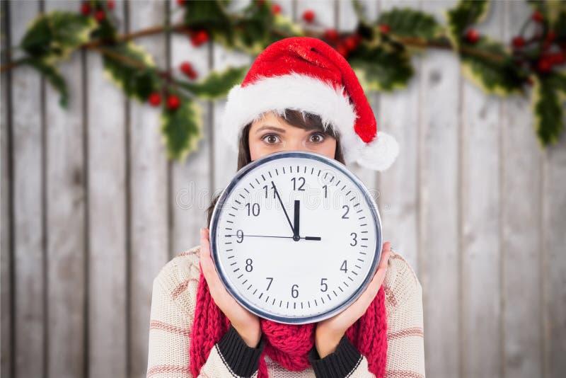 Γυναίκα στο καπέλο santa που κρατά ένα ρολόι τοίχων στο ψηφιακά παραγμένο κλίμα στοκ φωτογραφία με δικαίωμα ελεύθερης χρήσης