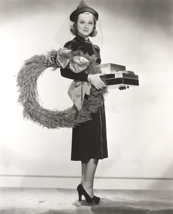 Γυναίκα στο καλυμμένα φέρνοντας στεφάνι και τα χριστουγεννιάτικα δώρα καπέλων στοκ εικόνα με δικαίωμα ελεύθερης χρήσης