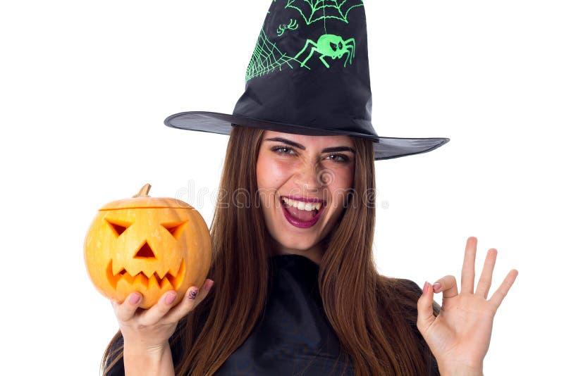 Γυναίκα στο κοστούμι της μάγισσας που κρατά μια κολοκύθα και που παρουσιάζει ο.κ. στοκ εικόνα με δικαίωμα ελεύθερης χρήσης