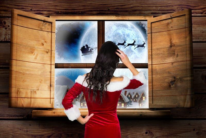 Γυναίκα στο κοστούμι santa που κοιτάζει μέσω του παραθύρου στοκ εικόνα με δικαίωμα ελεύθερης χρήσης