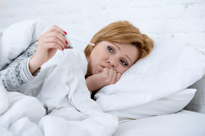 γυναίκα στο κρεβάτι με τον εμπύρετο αδύνατο υφιστάμενο ιό χειμερινής κρύο γρίπης θερμομέτρων στοκ εικόνα με δικαίωμα ελεύθερης χρήσης