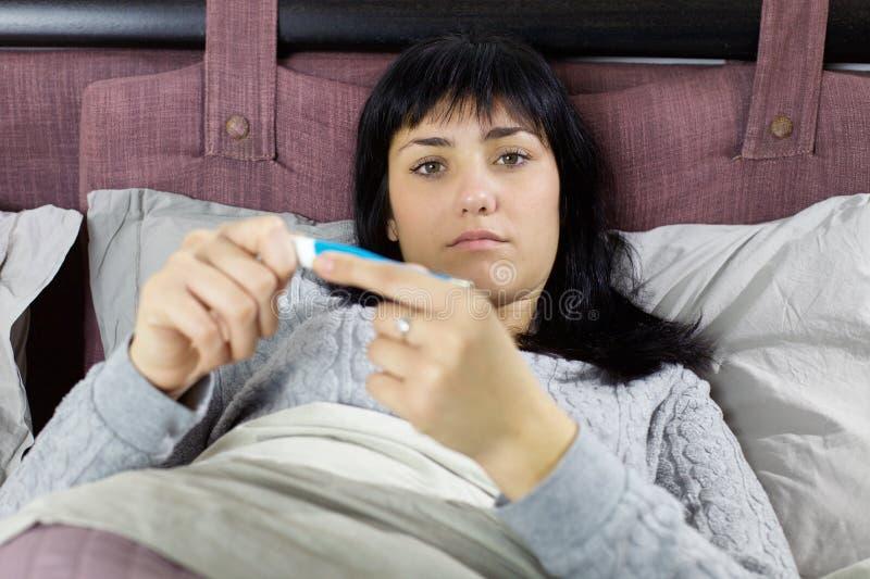 Γυναίκα στο κρεβάτι που ελέγχει τη θερμοκρασία που αισθάνεται άρρωστη στοκ εικόνες