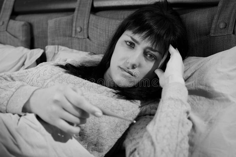 Γυναίκα στο κρεβάτι που ελέγχει το θερμόμετρο εκμετάλλευσης θερμοκρασίας γραπτό στοκ εικόνα με δικαίωμα ελεύθερης χρήσης