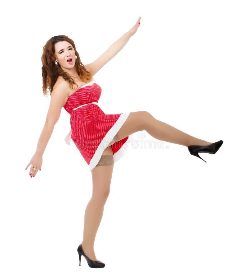 Γυναίκα στο κόκκινο λάκτισμα φορεμάτων στοκ εικόνα