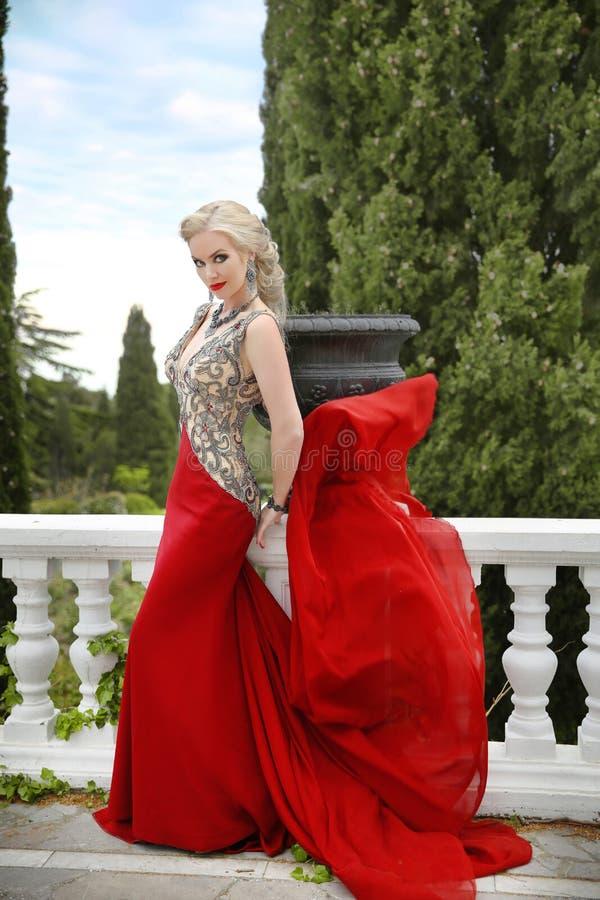 Γυναίκα στο κόκκινο κυματίζοντας φόρεμα Ξανθό πρότυπο μόδας στη φυσώντας εσθήτα ο στοκ εικόνες