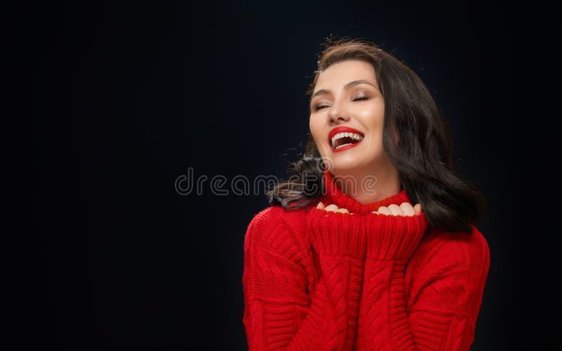 Γυναίκα στο κόκκινο πουλόβερ στο μαύρο υπόβαθρο στοκ εικόνα