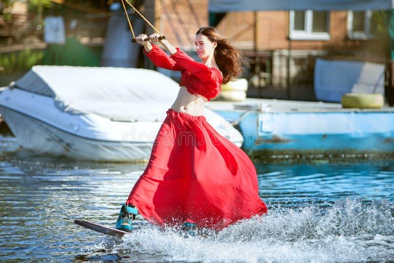 Γυναίκα στο κόκκινο σε ένα wakeboard στοκ φωτογραφίες με δικαίωμα ελεύθερης χρήσης