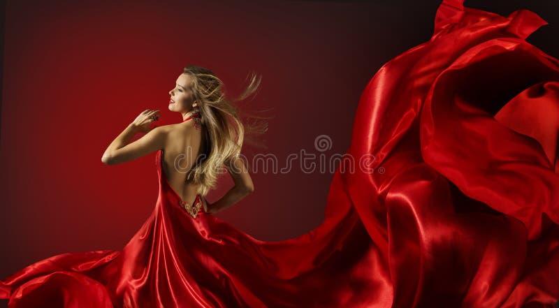 Γυναίκα στο κόκκινο φόρεμα που χορεύει, πρότυπο μόδας με το πετώντας ύφασμα στοκ εικόνα