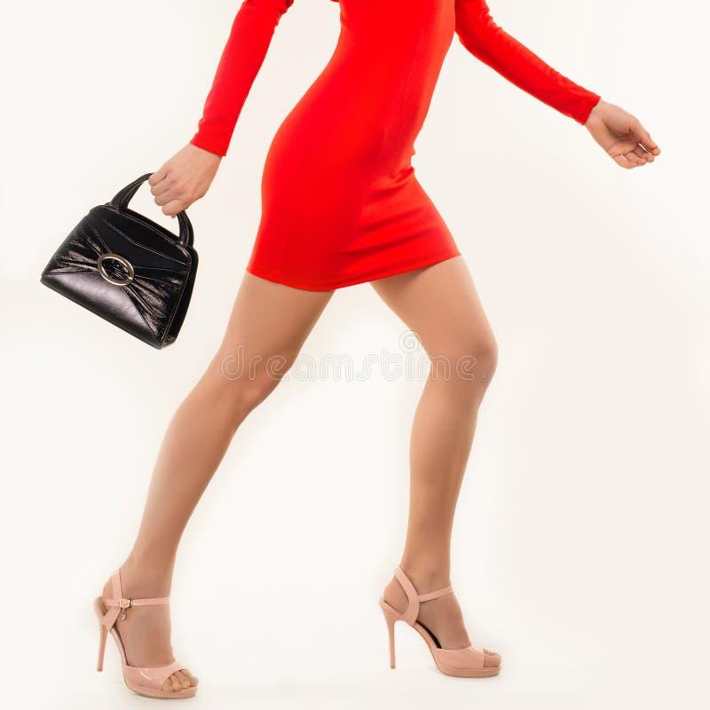 Γυναίκα στο κόκκινο φόρεμα στα υψηλά τακούνια με την τσάντα στοκ φωτογραφίες
