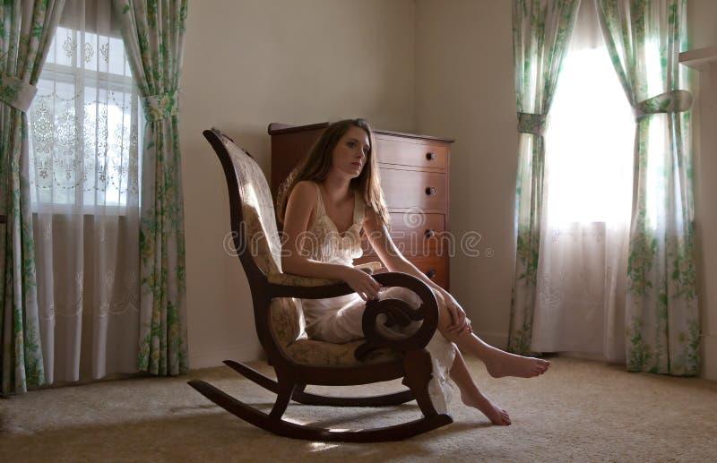 Γυναίκα στο λίκνισμα της έδρας στο όμορφο δωμάτιο στοκ εικόνες