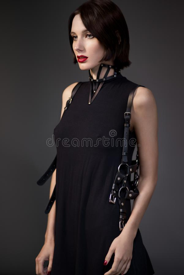 Γυναίκα στο μαύρο φόρεμα με τα εξαρτήματα δέρματος στοκ εικόνες