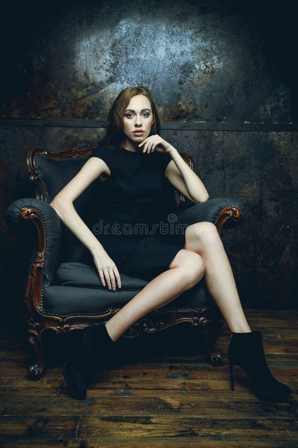 Γυναίκα στο μαύρο φόρεμα στην καρέκλα στοκ εικόνα